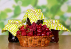 Basket strawberries, raspberries and cherries, jars jam on abstract green . Royalty Free Stock Photo
