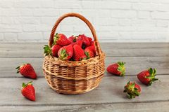 Basket with strawberries, some of them spilled on gray wood desk.  Royalty Free Stock Images