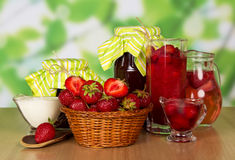 Basket strawberries, spoon, jars jam, beverages, cream on abstract green. Stock Photo