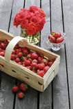 Basket of strawberries on wooden table. Bouquet of red roses in Royalty Free Stock Photography