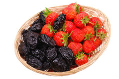Basket with strawberry and prune on white Stock Photos
