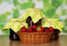 Basket with strawberry and three jam banks Royalty Free Stock Photo