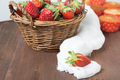 Basket of strawberry on wooden table. Basket of strawberry on brown wooden table and one strawberry in focus with some muffins on background Stock Images