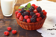 Basket of summer berries and milk cup on wooden table. Basket of blackberries, strawberries and raspberries and cup of milk on wooden table. Rustic style Stock Images