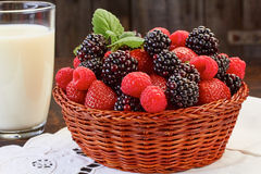 Basket of summer berries and milk cup on wooden table Stock Image
