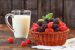 Basket of summer berries and milk cup on wooden table. Basket of blackberries, strawberries and raspberries and cup of milk on wooden table. Rustic style Stock Photo