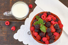 Basket of summer berries and milk cup on wooden table. Basket of blackberries, strawberries and raspberries and cup of milk on wooden table. Rustic style, top Stock Photo