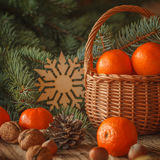 Basket with tangerines, cones, nuts and fir Royalty Free Stock Photos