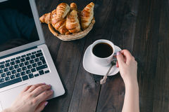Basket with tasty fresh croissants and hot morning cup of coffee Royalty Free Stock Image
