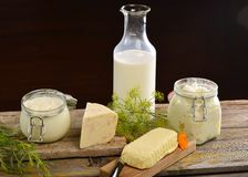 Basket with tasty organic dairy products on wooden table, Royalty Free Stock Images