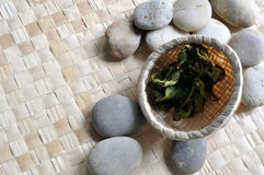 Basket of tea leaves on pebbles. A bamboo basket of tea leaves rest on a mat with some pebbles Royalty Free Stock Images