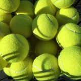 Basket of tennis balls. A close up of a basket of tennis balls in the sun Royalty Free Stock Photos