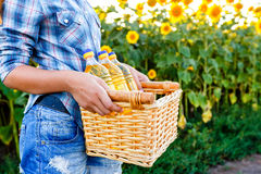 Basket with three bottles of sunflower oil in hands of girl Stock Photo