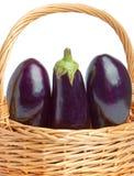 Basket and three ripe eggplant Stock Photos