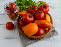 Basket with tomatoes of different varieties and arugula sheaf on white wooden background Royalty Free Stock Photo