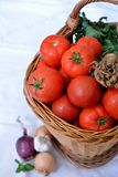 Basket of tomatoes. Fresh red tomatoes ad other vegetables in basket  on white vertical background Stock Photography