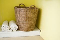 Basket and towels. Big basket and towels with yellow wall Stock Photography
