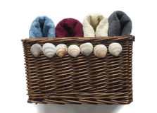 Basket of towels. Basket of multi coloured towels decorated with sea shells isolated on a white background Royalty Free Stock Photos