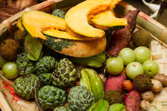 Basket with tropical fruits and vegetables. Set of tropical fruits and vegetables. Fruits and vegetables for the holiday table. The rich harvest of fruits and Stock Photos