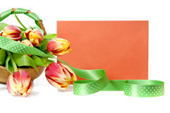 Basket of tulips and an orange envelope Royalty Free Stock Image