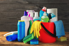 Basket with variety cleaning product on wooden table royalty free stock images