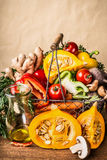 Basket with various autumn seasonal organic harvest vegetables and pumpkin at wall background, front view. Autumn food Stock Image