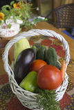 Basket with vegetables. The basket of vegetables on the table, summer terrace royalty free stock images