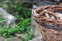 Basket in the village. Wicker basket stands on a green background somewhere in the village Stock Image