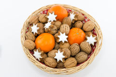 Basket with Walnuts, Tangerines and Cinnamon Stars Royalty Free Stock Photography