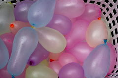Basket of water ballons. White basket of pink, purple and blue water ballons Stock Image