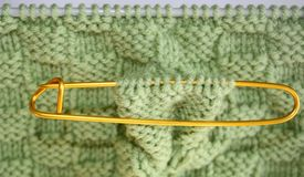 Basket weave pattern knitted on knitting needles in sage green color wool.   Stitch holder in place marking off extra stitches to Royalty Free Stock Photography
