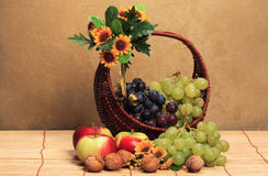 Basket whit fruits. Apples, grapes, nuts Stock Images