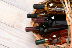 Basket of Wine Bottles. A high angle shot of wine bottles in a basket on a whitewashed wood farmhouse style kitchen table. Horizontal format with copy space Stock Images