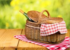 Picnic Basket with wine and cloth on table. Basket wine picnic leisure table green red Stock Photo