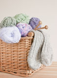 Basket with wool, knitting needles and socks. Wicker basket filled with colourful wool and yarn. Wooden knitting needles and a pair of knitted woollen warm stock image