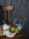 Basket with wool yarn and knitting, books and a toy bear on the old chair Stock Image