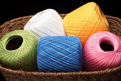Basket of Yarn (close view). A woven basket filled with colorful spools of yarn royalty free stock photos