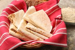 Basket with yummy tortillas. On kitchen table Royalty Free Stock Image