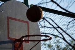 Basketbal die door de mand bij een opzettelijke schijnwerper van de sportenarena gaan royalty-vrije stock foto's
