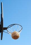 Basketbal in het net tegen duidelijke blauwe hemel Stock Afbeeldingen