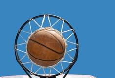 Basketbal in het net tegen duidelijke blauwe hemelen Stock Foto's