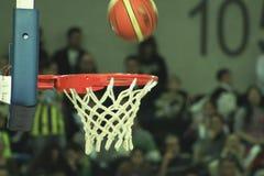 basketbal terwijl in de mand binnengaat Royalty-vrije Stock Afbeeldingen