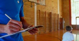Basketbalbus die op een blocnote in basketbalhof op school 4k schrijven stock footage