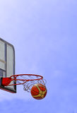 Basketball. A basketball swishes through the hoop- streetball match detail Royalty Free Stock Photography