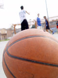 Basketball and 3 players. A ball in a basketball court and 3 players on the background Stock Photography