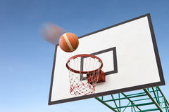 Basketball in air over hoop Royalty Free Stock Photography