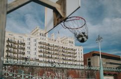 Basketball ambience in the city. Basket ball entering into a basketball ring, at an urban court, with the focus in the background stock photography