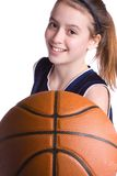 Basketball Anyone?. Young girl in a jersey holding out a basketball as if inviting some to play Royalty Free Stock Image