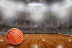 Basketball Arena With Ball on Court and Copy Space. Low angle view of fictitious basketball arena with sports fans in the stands. Focus on foreground with Stock Photography