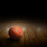 Basketball Arena With Ball on Court and Copy Space. Basketball arena with ball on court and special lighting effect. Copy space Royalty Free Stock Image